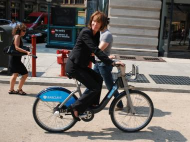 DOT Commissioner Janette Sadik-Khan rides one of the bikes through a public plaza.