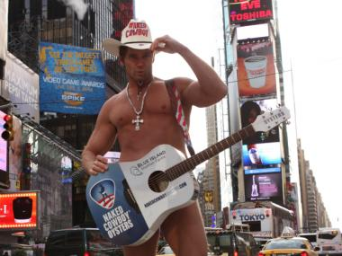 Naked Cowboy Robert Burck poses with his branded, Naked Cowboy oyster guitar.