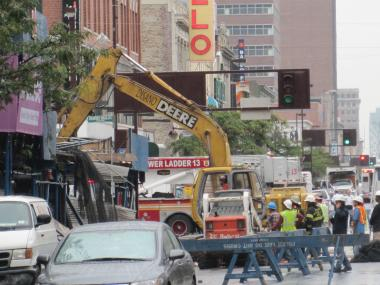 Workers demolish part of a building that partially collapsed along with its scaffolding Tuesday.
