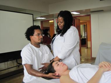 New York College of Health Professions instructor Leslie Brown teaches Ron Thomas about proper breathing techniques.