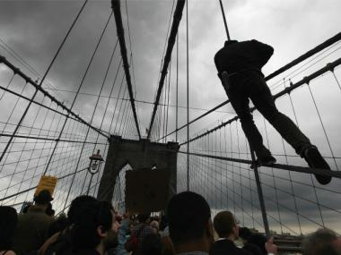 A man scales the support cables above the pedestrian walkway as demonstrators affiliated with the Occupy Wall Street movement attempt to cross the Brooklyn Bridge on the motorway below on October 1, 2011 in New York City.
