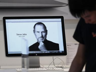 A man looks over Apple products displaying a tribute to Steve Jobs, co-founder and former chief executive officer of Apple, at a store in Marina Bay Sands, Singapore on Thursday, Oct. 6, 2011.