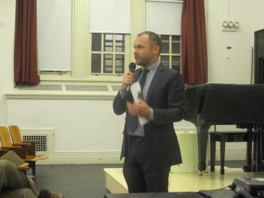 Community Board 4 Chair Corey Johnson speaks before a crowd at a public meeting.