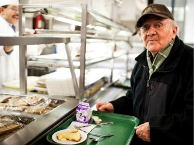 "A man takes food at a soup kitchen in the Food Bank For New York network. Soup kitchens and pantries have seen ""near record level"" needs, experts say."