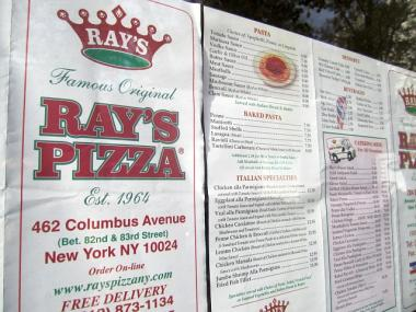 Menus from Famous Original Ray's were on display in the newspaper-covered windows of the eatery, when DNAinfo stopped by on Dec. 2, 2011.