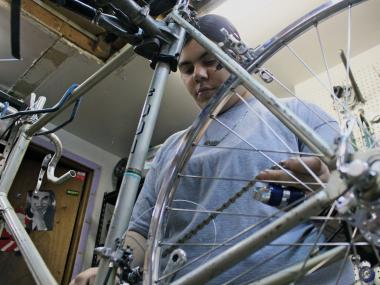 Natalie Feliciano works on a bike in the East Village store and workshop of Recycle-a-Bicycle, a member of Local Spokes.
