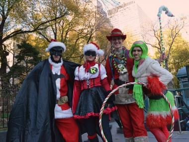 "Friends ""Bruce Wayne,"" Whitney Thielman, 23, Mitch Gerbus, 28, and Jewels Ziff Sint, 31, dressed as their version of Santa-Batman and his elves for SantaCon near City Hall on Dec. 10, 2011."