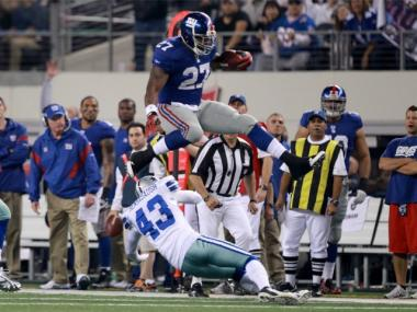 Giants running back Brandon Jacobs leaps a Cowboys defender during a 37-34 win over Dallas on Dec. 11, 2011.