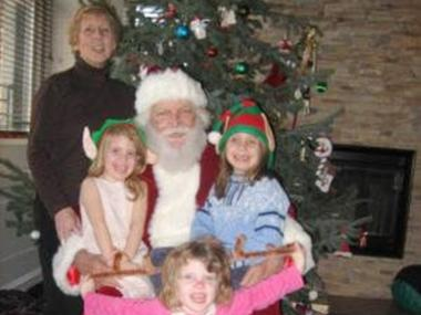 Lomer Johnson, dressed as Santa, with his wife and three granddaughters — all of whom died in the Christmas Day blaze.