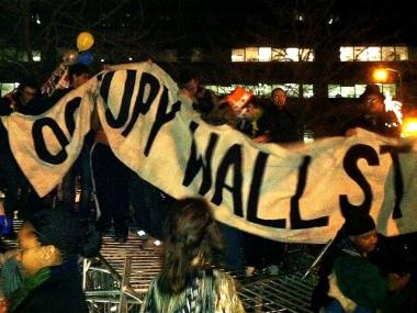Occupy Wall Street protesters hold up a sign in Zuccotti Park after protesters stacked up barricades there on Dec. 31, 2011.