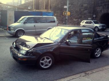 A car's hood is smashed after an accident with a school bus at 104th Street and Park Avenue on Jan. 3, 2012.