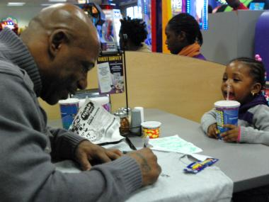 Carl Robinson and his two-year-old daughter, Autumn, decorate T-shirts at Chuck E. Cheese's in the Bronx on Jan. 14, 2012.