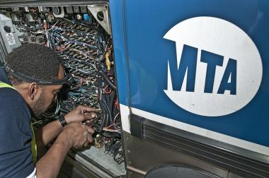 A worker installs tracking hardware on a Staten Island MTA bus in November 2011.  MTA workers will soon install the equipment in Bronx buses.