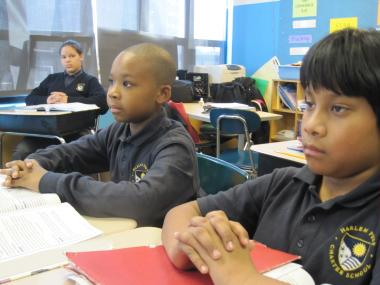 Students in a fourth-grade class at Harlem Prep focus after their teacher rings a bell.