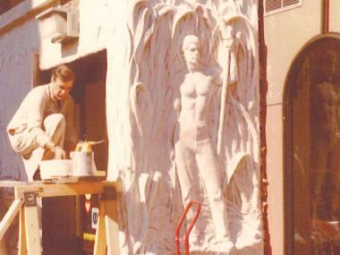 Sculptor Arturo Martin Garcia with the mural he created outside Victor's Cafe in the 1970s.