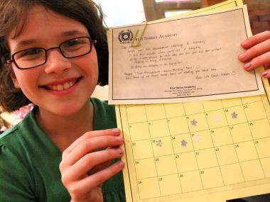 Katherine Happy holds up a star chart that helps her stay on task to reach goals like doing homework.