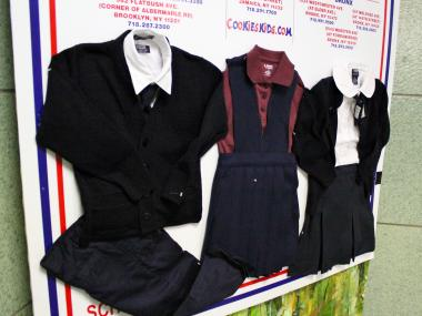 A likeness of uniforms for P.S. 64 are on display in the schools foyer. The uniform will consist of a white shirt, grey pant or skirt, a maroon sweater and a maroon tie or bow
