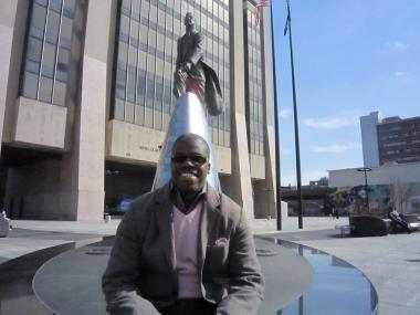 TEDxHarlem Executive Director Imari Oliver in front of a statue of Adam Clayton Powell Jr. on 125th Street.