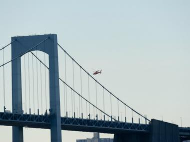 A helicopter hovers near the Throgs Neck Bridge, where a construction fell on Fri., March 30, 2012.