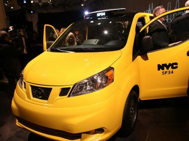 : People look at the new New York City taxi which is designed by the Nissan Motor Co. at an official unveiling on April 3, 2012 in New York City. The new taxis, which will start appearing on the streets of New York next year, service an estimated service 600,000 people daily. The 2014 NV200 Taxi will replace the fleet of iconic Ford Crown Victorias, Ford Escape Hybrids and Toyota Siennas that are currently being used. Some of the highlights of the new taxi include front and rear-seat occupant curtain airbags, a window on the roof, backseat cellphone charging and USB ports and passenger reading lights.