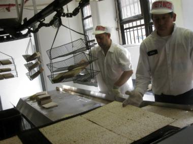 Workers at Streit's Matzos pull the freshly made unleavened bread off a conveyor belt.