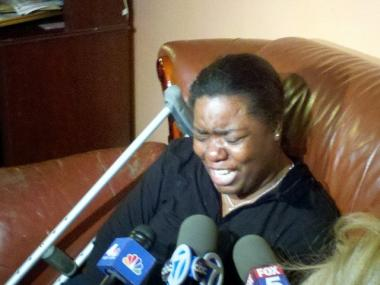 Mislov Aleger weeps as she talks about her husband, Francky Aleger, an auxiliary cop who was shot to death near his home in Canarsie on April 4, 2012.