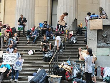 Occupy Wall Street protesters hang out on the steps of the Federal Hall National Memorial after police pushed them off the Wall Street sidewalk, April 16, 2012.