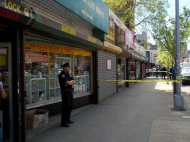 A police officer stands guard in East Harlem, after a police officer was stabbed in the neck on April 17, 2012.