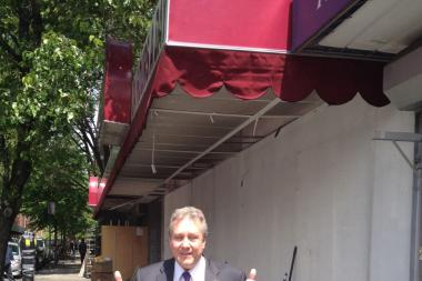 Dromm poses on the sidewalk, where Trade Fair's enclosure once stood.