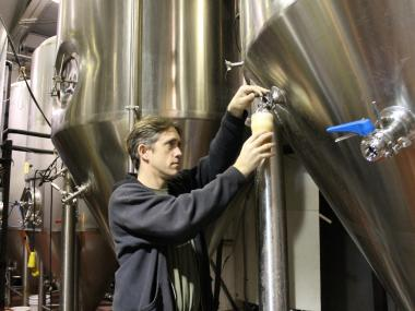 Kelly Taylor, who owns Kelso of Brooklyn brewery along with his wife, tasted a new Kelso Pale Ale from a fermenter in his brewery. Taylor increased his prices on beer by $4 a keg this week.