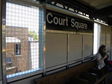 The platform at the Court Square station is about 10 to 15 feet from residents' bedroom windows, and divided only by transparent mesh windscreens.