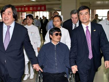 Chinese dissident Chen Guangcheng, who may soon be a scholar at NYU, holds hands with U.S. Ambassador to China Gary Locke, right, May 2, 2012.