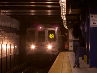 An R train approaches the 74th St - Roosevelt Ave station