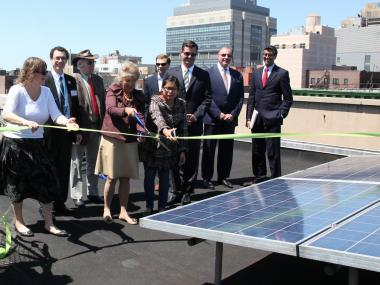 Community leaders participate in a ribbon cutting to celebrate NMIC's unveiling of its solar panel system in Washington Heights on May 17, 2012.
