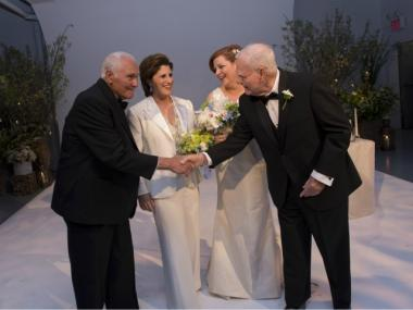 City Council Speaker Christine Quinn and her wife, Kim Catullo, embrace their fathers, who walked them down the aisle.