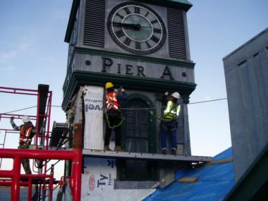 Workers are repairing Pier A's clock tower.