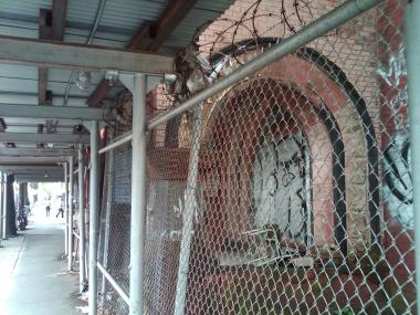 The former stationhouse is now surrounded by a rotten sidewalk shed, rusting chain link fences and barbed wire.