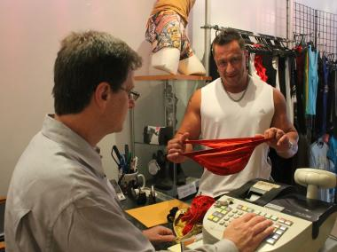 German bodybuilder Oliver Nickel-Glücklich examines a posing suit.