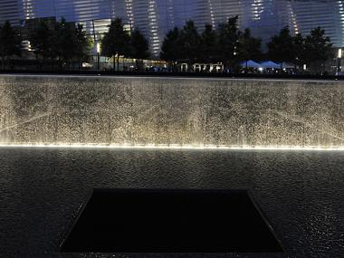 The 9/11 Memorial reflecting pool lit up at night.