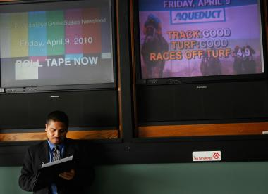 A job seeker in front of television screens April 9, 2010 at the Aqueduct Race Track in the Jamaica neighborhood, in Queens, New York.