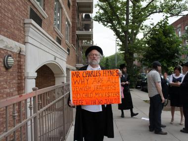 A protester outside Crown Heights Ohel Nosson Shul on Sunday, June 10, 2012 holds a sign decrying Kings County District Attorney Charles Hynes for his controversial policy of withholding the names of accused and convicted pedophiles from Orthodox Jewish communities across Brooklyn.