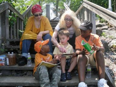 Dr. Carole Reiss, founder and director to the Staten Island Green Charter School, reading to children at Buono Beach, Rosebank.