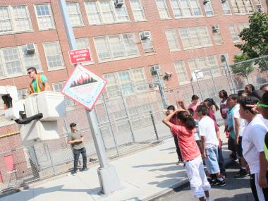 Fifth grade student from P.S 64 watch as a street sign with their own design is attached to a light post on East Fifth Street.
