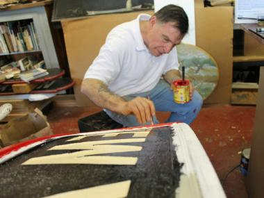 Sal Polisi paints a sign that will go on one of the Seaport Museum's boats.
