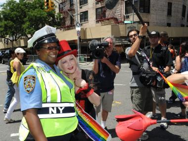 NYPD officer Tracey Jacobs poses with Grand Marshal Cyndi Lauper on Washington Street on June 24, 2012.