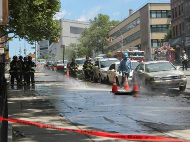 Firefighters sprayed down a smoking manhole on Wednesday after an underground explosion sparked a fire.