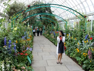 "A visitor strolling through the Grande Allée in the Botanical Garden's latest exhibition, ""Monet's Garden."""