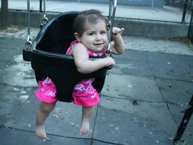 A 7-month-old baby swings in Washington Hall Playground.