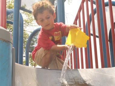 Jacob, 9, pours water on a slide at Russell Sage playground to cool it down.