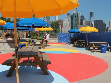 Brightly colored picnic tables available to sit and eat hot dogs and hamburgers sold at the Beach Shack.
